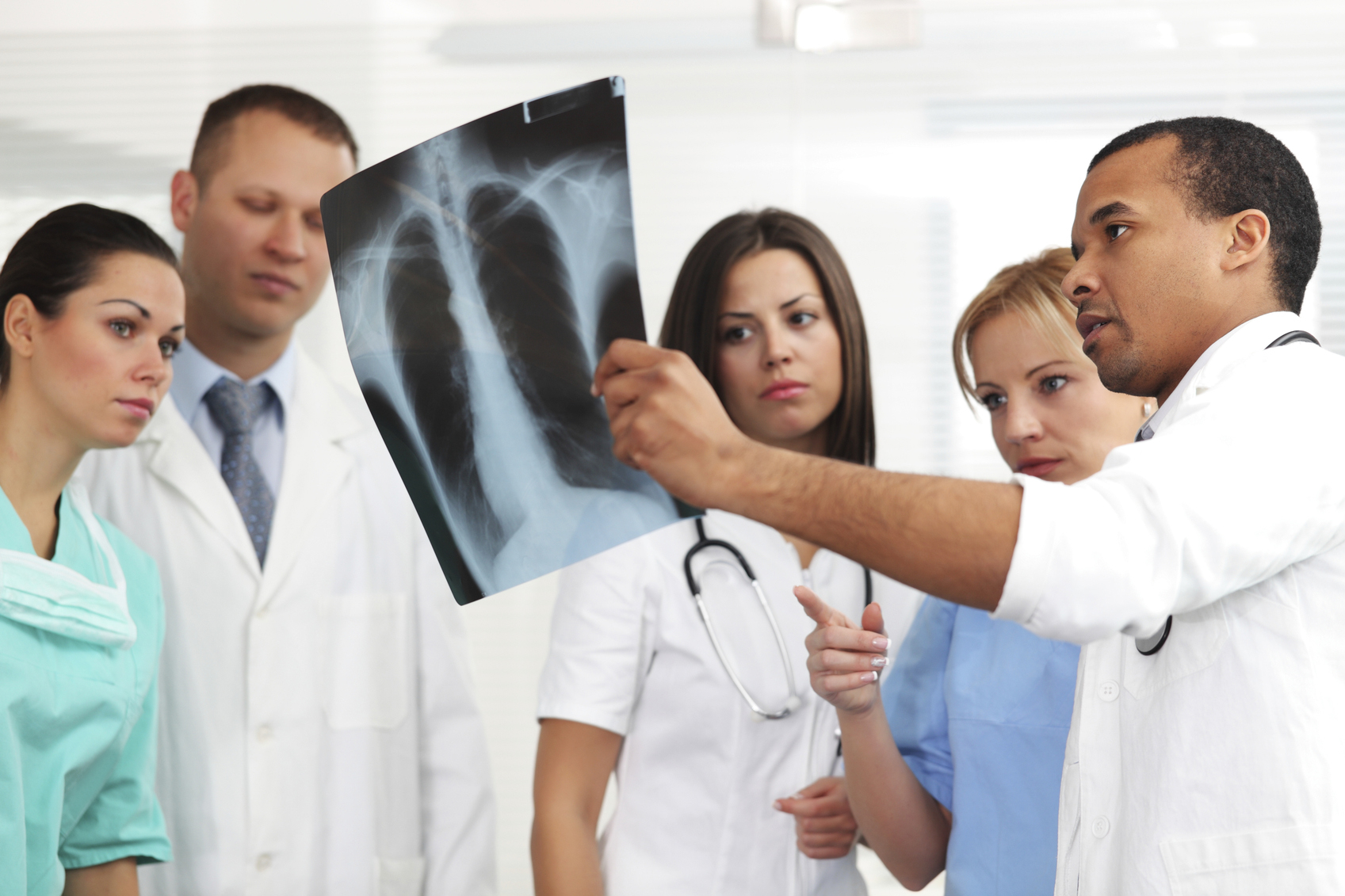 Doctors and nurses looking at patients x-ray.
